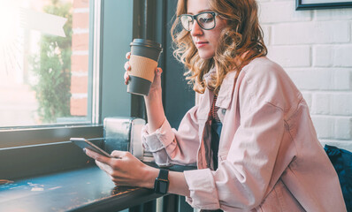 Hipster girl sitting in cafe at black table, drinking coffee and using smartphone. Businesswoman working online.