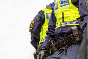 Two police officers, close up of upper body with vest and equipment belt.