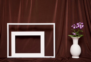 Two empty picture frames and vase with flowers on background of brown cloth.