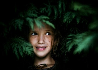 Smiling Girl Standing By Tree In Park