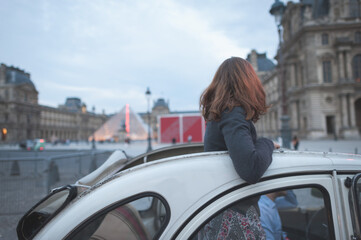 Woman Standing In Vintage Car In City
