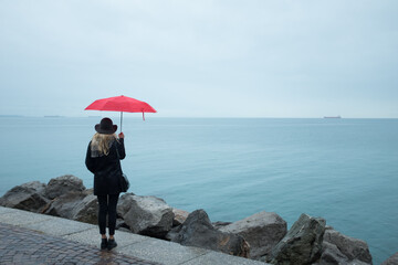 Woman Carrying Red Umbrella Standing At Sea Shore