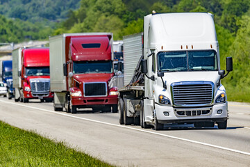 A solid line of eighteen-wheelers barrel down an interstate highway in Tennessee.  Heat waves rising from the pavement give a nice shimmering effect to vehicles and trees behind the lead truck. Wall mural