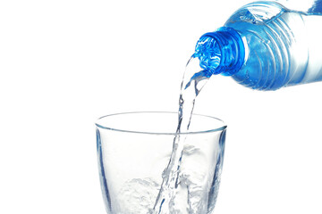 Water pouring from bottle into glass on white background