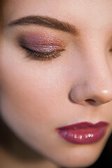 Vertical close-up of woman with bright makeup in mauve colors with eyes closed. Nude visage with perfect eyebrow shape and sparkle eyeshadow pigment
