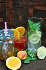 Glasses with refreshing drinks with fruits and herbs on an old wooden background