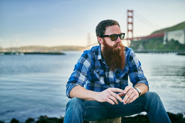 cool bearded hipster chilling out by the bay in front of the golden gate bridge in san francisco