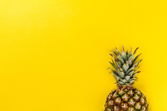 Half slice of beautiful fresh appetizing tasty pineapple on yellow bright background. Top View. Horizontal. Copy Space. Conceptual.