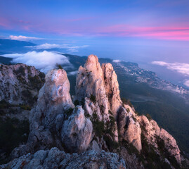 Wall Mural - Mountain landscape at sunset. Amazing view from mountain peak on the high rocks, blue sky, red clouds and sea in the evening. Low clouds. Colorful nature background. Adventure. Travel in Crimea