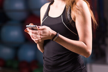 Young woman with fitness tracker and smartphone in gym