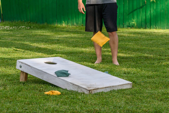 guy playing bags game out in backyard on sunny summer day