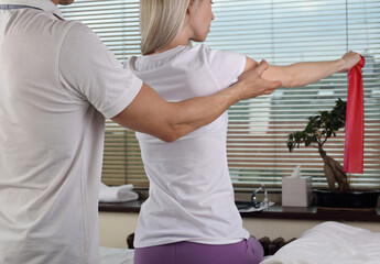 Physiotherapy, sport injury rehabilitation treatment with Resistance Band. Woman having chiropractic back adjustment. Osteopathy, Alternative medicine, pain relief concept.