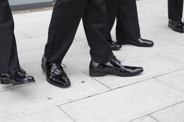 Feet and legs of male wedding party wearing black tuxedoes and black shiny shoes