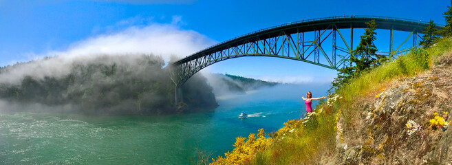 Woman meditating on seashore by the bridge. Deception Pass Bridge.  Anacortes. Whidbey Island....