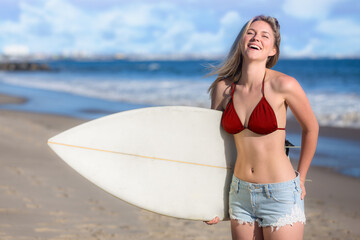 Playful laughing all american california blonde girl next door holding surfboard at the beach