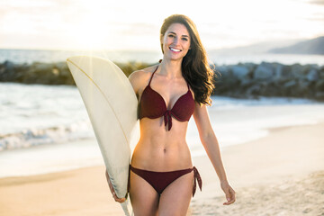 Surfer girl fit toned body happy smile beautiful model active fitness during sunset at the beach