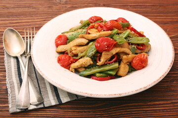 Stewed chicken breast with green bell pepper, young peas and tom