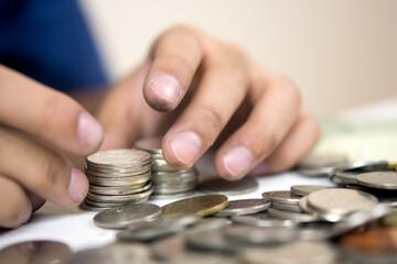 Blur  coine and boy hand .selective focus  on coine .money