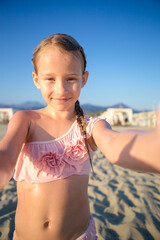 Happy little girl taking selfie at european beach during summer vacation in Italy
