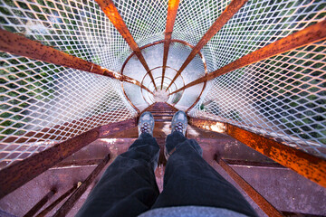 POV looking down a rusted old ladder on a water tower