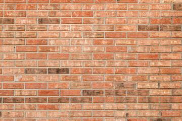 Brick wall with orange, brown and white bricks.