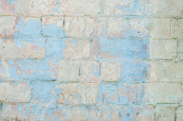 An old painted wall with a peeling blue paint from a large brick. Vintage texture. Red brick.
