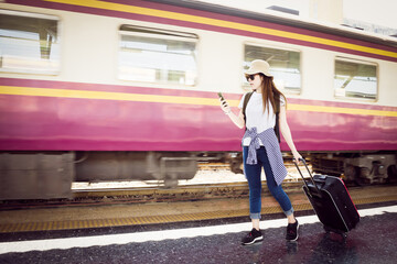 Cute asian traveler woman using smartphone and walking with luggage at train station. Traveling summer concept
