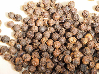Closeup image of black peppercorns on a wooden board