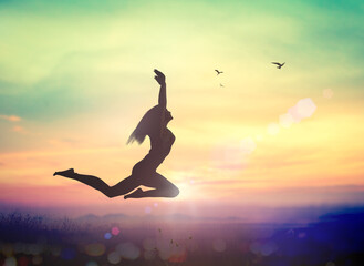 International human rights day concept: Silhouette of a girl jumping at autumn sunset mountain with her hands raised
