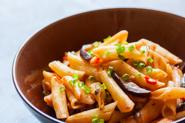 Close up of italian penne pasta with eggplants and tomato sauce in a brown bowl on a white stone background. Copy space and overhead view. Traditional food concept.