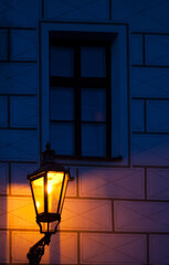 Vintage lamp illuminating the ancient wall with window at night
