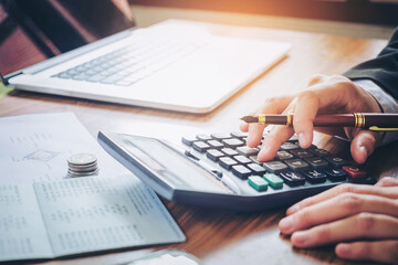 Businessman's hands with calculator and cost at the office and Financial data analyzing counting on wood desk