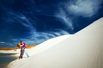 lovers embracing on beach with white sand