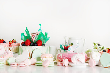 Candy bar with cakes, muffins, meringues, macaroons and biscuits. Pastel shades. Children's holiday.