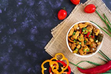 Stir Fry Chicken with peppers and mushrooms on dark background. Top view