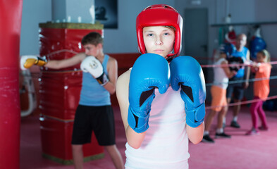 Teenage boy boxer posing during boxing exercising