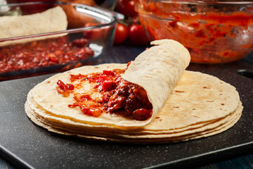 Preparation traditional mexican enchiladas with chicken meat, spicy tomato sauce and cheese