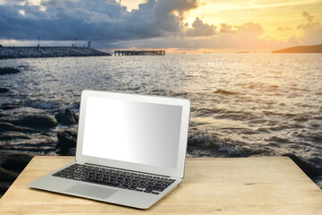 laptop on wood table with seascape background