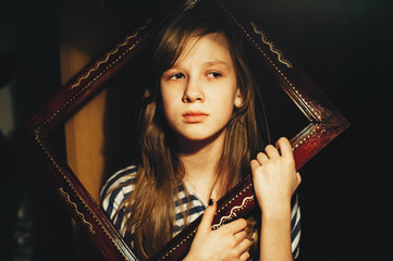 Portrait of a sad little girl looking out of a wooden frame. Child. Atmospheric photography. Conceptual.