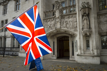 British Union Jack flag flying in front of The Supreme Court of the United Kingdom in the public Middlesex Guildhall building in Parliament Square in London