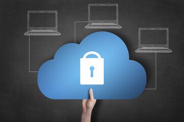 Businessman is holding a blue cloud icon on blackboard. Network security concept.