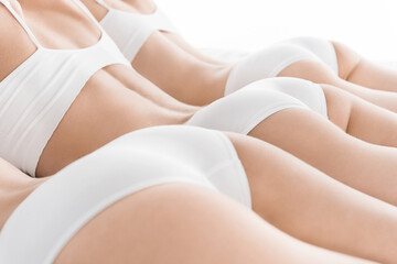 cropped rear view of young women in white underwear lying on bed