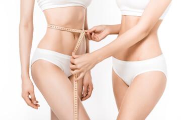 cropped shot of girls using measuring tape to assess waist volume