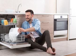 Man unloading dishwasher