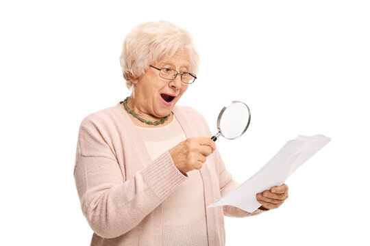 Surprised mature woman looking at a document through magnifying glass
