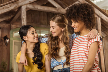 Multiethnic group of beautiful smiling young women standing embracing on porch