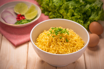Instant noodles in bowl with vegetables on wood background