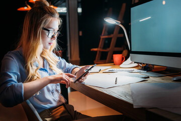 young blonde caucasian businesswoman in eyeglasses using smartphone and sitting at workplace with computer