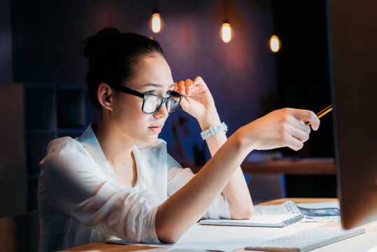 concentrated asian businesswoman in eyeglasses pointing at computer monitor, working late at the office