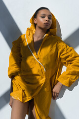 Beautiful seductive african american girl lying in yellow raincoat and looking at camera